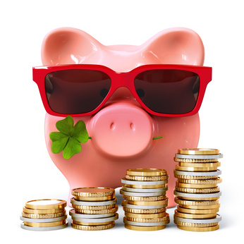 Easy life or rich life: Piggy bank with red sunglasses, clover and coin stacks