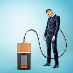 Is Lethargy in Your Business a Hidden Killer: A businessman who is being recharged by a battery