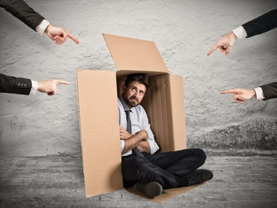 Fake news from the HR department: Guilty businessman indicated by colleagues hiding in a cardboard box