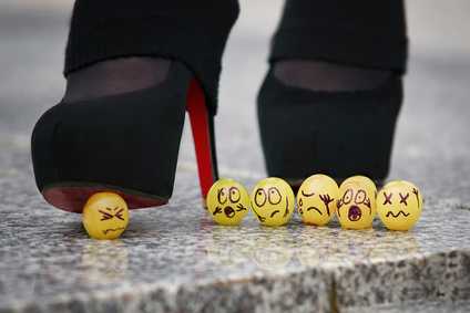 The danger of a narcissist on the team: Group of grapes looking scared as one is being crushed by a high heel
