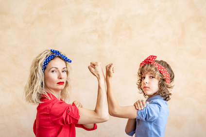 #MeToo behaviours: Two women wearing red and blue bandannas and tops flexing their arms to signify strength in women