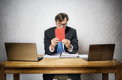 Businessman holding red card to signify reasons for dismissals